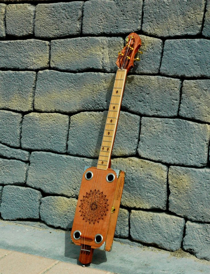 Handcrafted electric cigar box guitar with an intricate woodburned design on the body, the fretboard, and the headstock