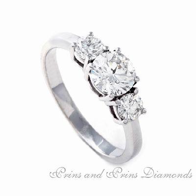 Centre diamond is a 0.711ct I/SI1 Round brilliant cut diamond with 2 = 0.50ctct GH/SI round brilliants set in a straight platinum band