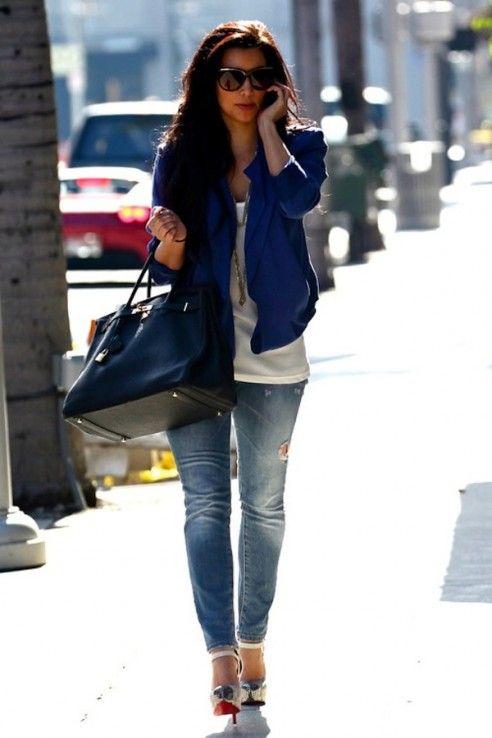 La chica llevando un chaqueta azul.  La chica llevando los jeans azul.  La chica llevando bolso azul marino.  Sú bolso cuesta setenta dolares.  Sú chaqueta cuarenta dolares.  Sú tacones altos cuesta cien dolares.