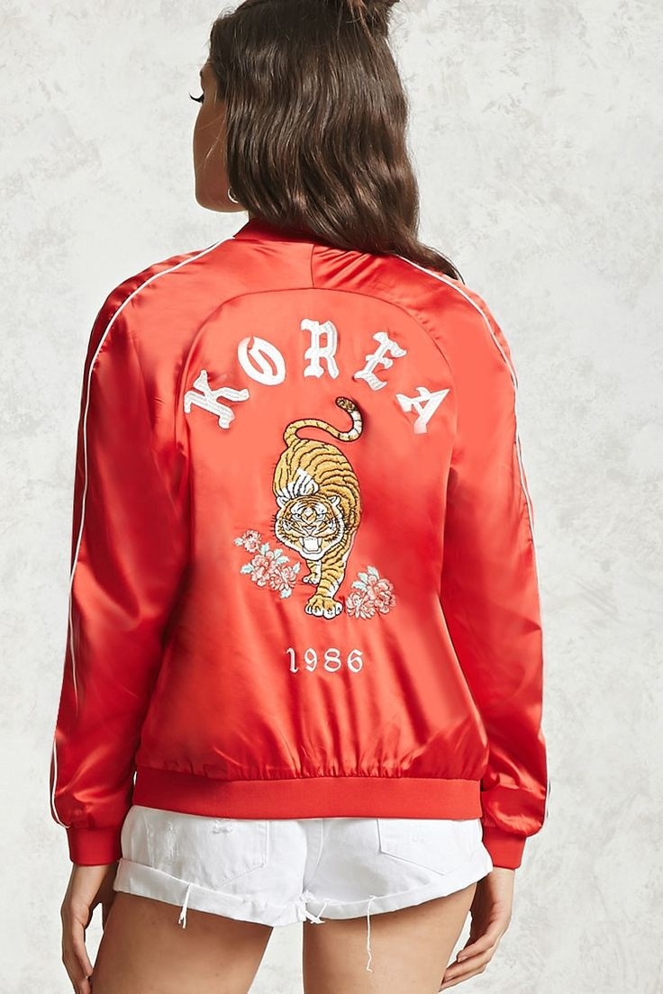 """A satin souvenir jacket featuring an embroidered tiger, florals, and """"Korea 1986"""" on the back, contrast piped trim, a zipper front, ribbed collar, front slant pockets, and long sleeves."""