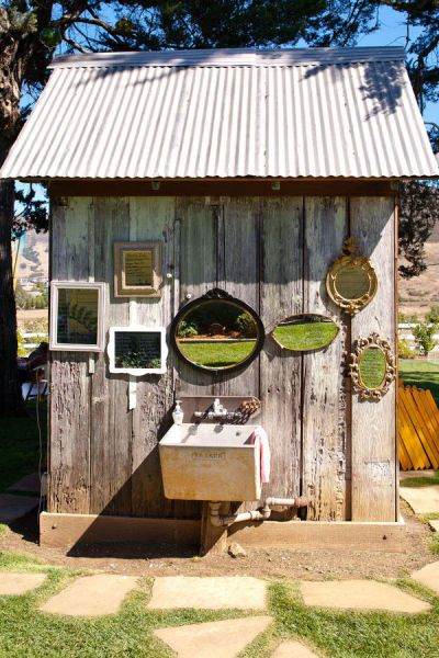 A rustic garden shed gets an instant makeover - try hanging thrift shop mirrors in clusters on the exterior of any outdoor structure that could use a facelift. #mirrormirroronthewall #gardens #thriftshopfinds