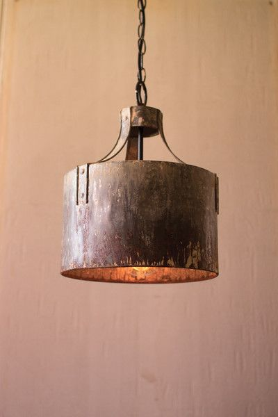 Rustic metal riveted arms clamp to a cylindrical pendant creating industrial light and more than a little magic. Pair two or more over a workspace or kitchen is