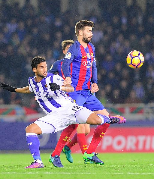 Real Sociedad's Brazilian forward Willian Jose vies with Barcelona's defender Gerard Pique during the Spanish league football match Real Sociedad vs...