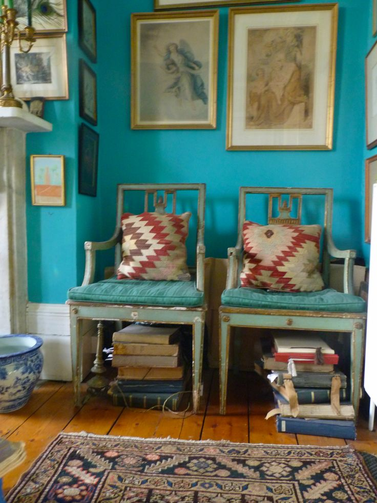 Bohemian at its best! - Turquoise wall - Old tribal rug - Vintage chairs with kilim rug pillows - Mismatched art - Wide plank wood floors