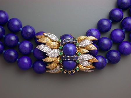 David Webb. Triple strand gem lapis lazuli bead choker, nested strands, with elegant chased gold, sapphire, emerald and diamond clasp worn at the center or to the side, ca. 1960.