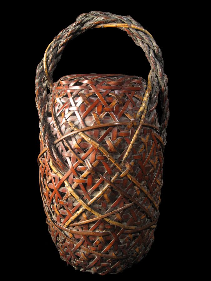Large ikebana basket with clematis plaiting body and rope and bamboo root handle .