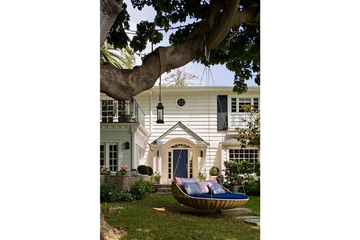 Colonial house front with a blue front door under a portico. Large oak tree has an inviting relaxing front yard swing bed - who needs a front porch swing? Add charming curb appeal to your home.