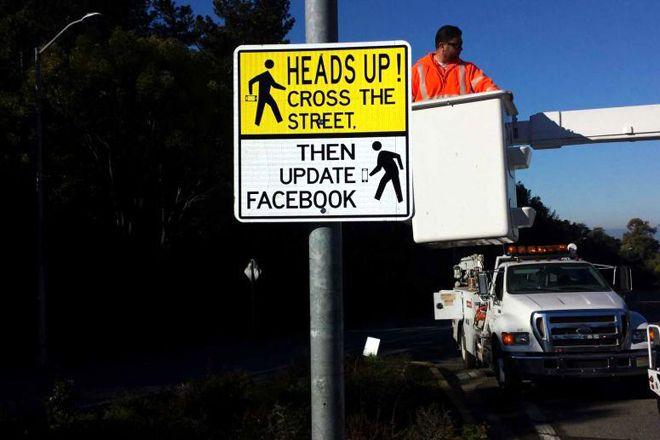 """Placa de sinalizaçao avisa – """"Atravesse a rua – e só entao atualize o Facebook"""""""