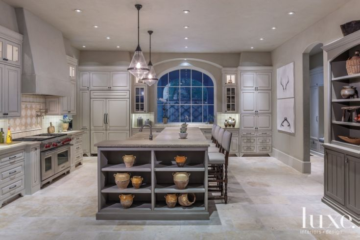 Pendants from Circa Lighting illuminate a distressed limestone-topped island from Alkusari Stone, which features a leather-like finish applied by Legacy Granite & Marble Co.