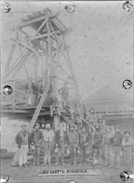 """Sepia - toned photograph of a group of miners standing against and near a poppet head. Inscription (label) glued onto front of photograph. Wording reads: """"Sergeant's Freehold"""" (this was the name of the mine).  Subject Date: unknown; Subject Location: Ballarat, Victoria, Australia. Courtesy of Ballarat Historical Society"""