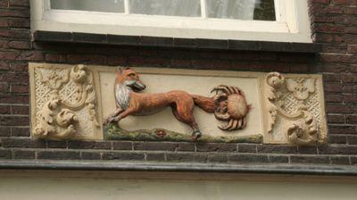 Gevelsteen De vos en de krab, op de Noordermarkt in Amsterdam. Het verhaal gaat over hoe de krab de vos tijdens een hardloopwedstrijd te slim af is door zich in zijn staart vast te bijten.
