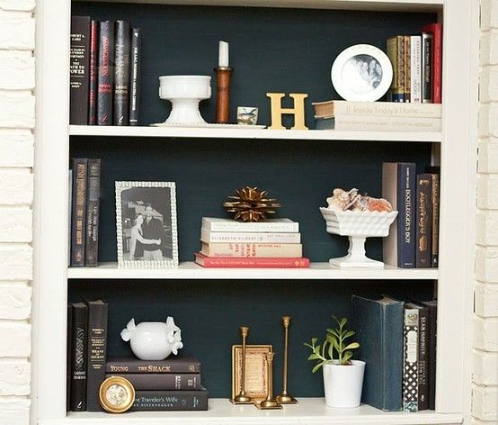 A good balance between books, accessories, and photos is key to achieving a well styled bookcase – via Cottage and Vine