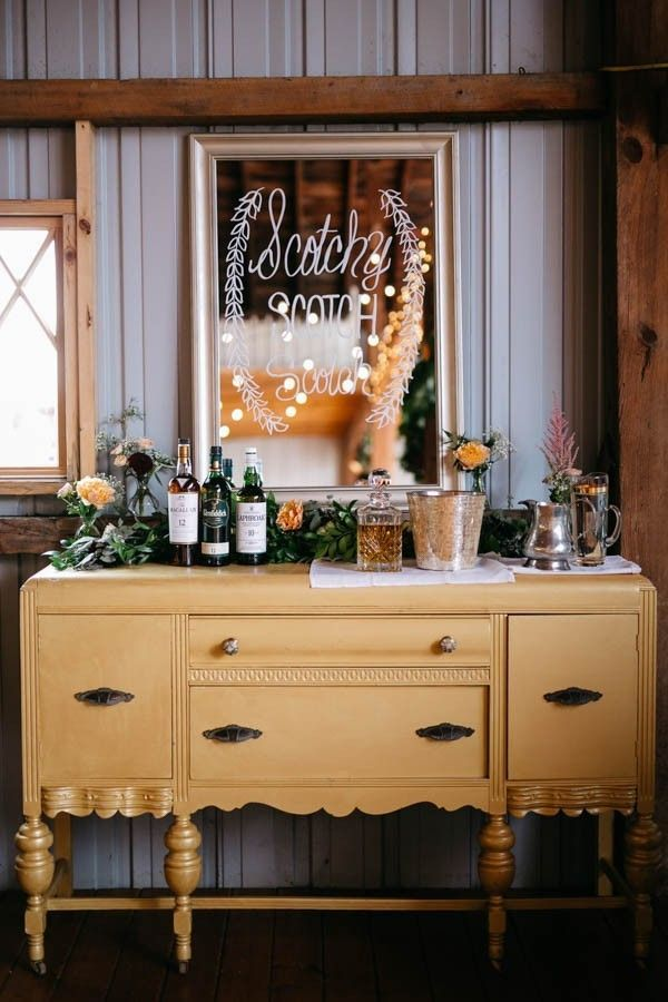 This Johnny Cash and June Carter inspired wedding in Michigan featured many nods to Southern hospitality, but this self-serve scotch bar takes the cake. Betsy and David set up their bar with a lush greenery garland, a DIY hand-lettered mirror sign, and classic scotch accoutrements like a crystal decanter and a silver whiskey pitcher. We love the idea of setting up a self-serve bar with the groom's favorite liquor as a fun, boozy alternative to a groom's cake that can be enjoyed by all…