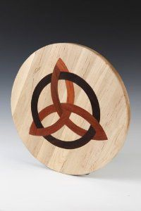 "Round cutting board with inlaid Celtic Trinity design by Kentucky Cutting Boards. $89.95. Inlaid with Celtic Trinity design of Purple Heart and African Wenge. www.kentuckycuttingboards.com. Board crafted of Appalachian Maple. 16"" diameter, 1 and 1/4 "" thick. Food Safe Glue. Kentucky Cutting Boards are Made in the USA.  All of our cutting boards are made from sustainable yield hardwoods and support our region's hardwood industry. The side or back of every board is st..."