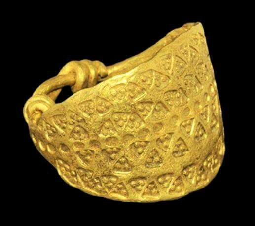 Viking Gold Ring with Stamped Triangles  9th-11th century AD.   A flat-section gold plaque with four rows of punched triangles, each with a pellet to each angle, and median row of roundels; to the reverse, two round-section extensions with each end coiled around the shank.   Ex Clements collection; acquired continental Europe 1950s; by descent, 2004. 9.46 grams, 23mm overall, 22.06mm internal diameter