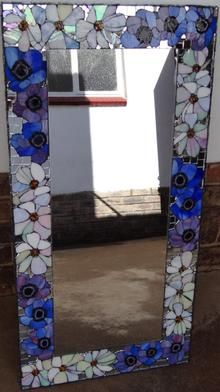 Rectangular mirror with glass mosaic flower motif border.