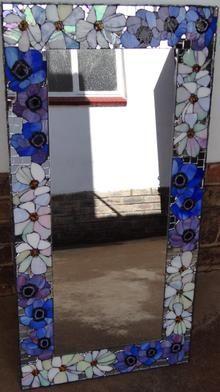 Rectangular mirror with glass mosaic flower motif border.