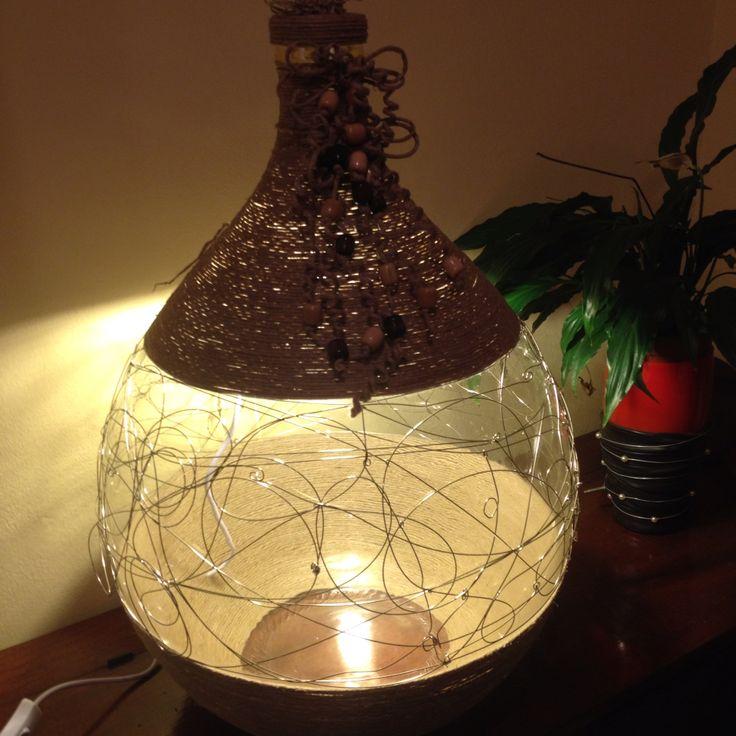 Artista Monica Bonaventura. Damigiana reciclata e riutilizzata per fare una lampada da terra. E' stata in parte ricoperta da spago e per la parte centrale è stato utilizzato acciaio inox scartato da una acciaieria.