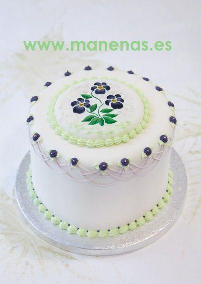 Tarta decorada con glasé real. Lleva además una decoración con plantilla. En este caso, la flor pintada se ha hecho con colorante en polvo. Use of the stencil on a fondant cake. En Manenas.