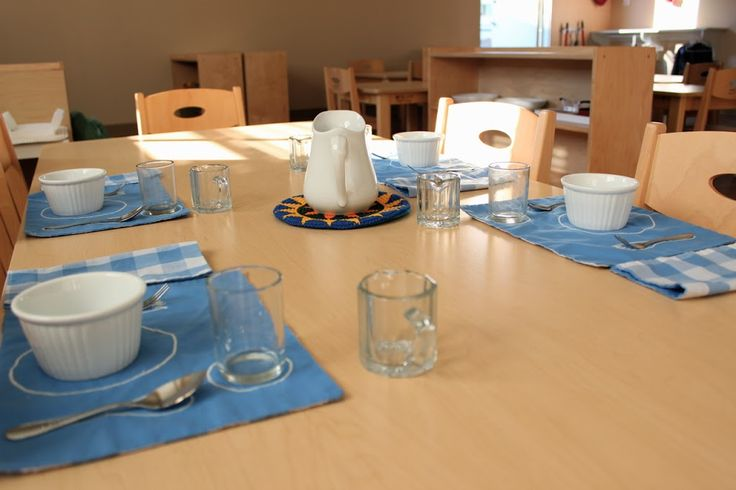 In our Montessori toddler rooms, the children learn to set their own table for snack. Beautiful materials, like these home-made place mats that show where all the utensils go, give every meal a festive touch.