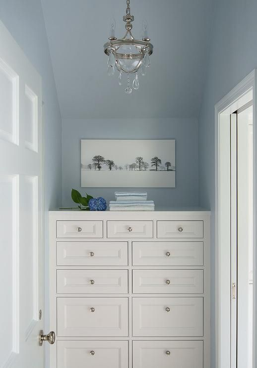 Blue bedroom nook illuminated by a glass tear drops chandelier features a white built in dresser adorning small nickel knobs and positioned under a sloped ceiling and a panoramic art piece. Circa Lighting Devon Mini Bowl Pendant