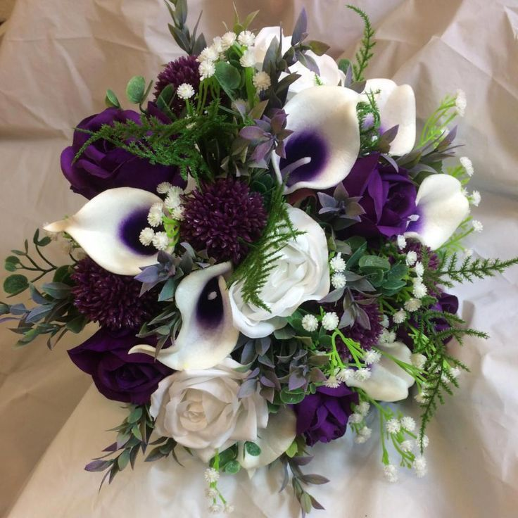 A wedding bouquet of white and purple silk flowers