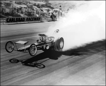 Vintage Dragster carrying the front wheels through a burnout.