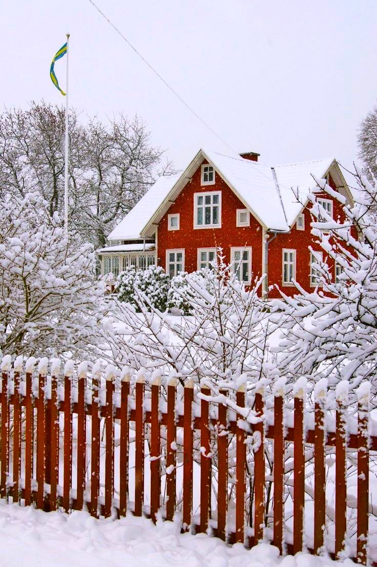 red house and fence in snow