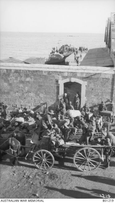 The 9th Australian Light Horse Regiment, embarking from the wharf. In the foreground soldiers are getting their kitbags from wagons. A door in a stone wall leads to the wharf. Lebanon, Tripoli 1918