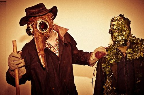 The Plague Doctor and Green Man at the Towner's Night Folk event (c) Kipperklock Photography. 2 people, one wearing a beaked plague doctor mask, one with leaves covering his face
