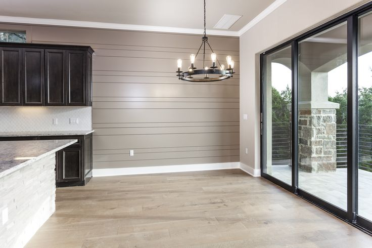 Transitional dining room for an Austin Texas spec home. Hill country contemporary style. Light Wood Floors, Dark bronze windows in Dining Room