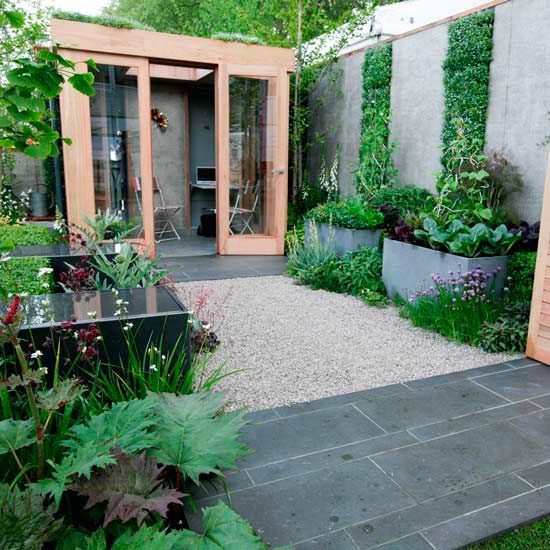 Urban garden with wooden garden room, slate patio, trellis planting and water feature