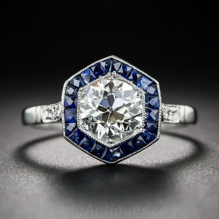Mano fabricada en duradero estilo Art Deco, este anillo de compromiso encantadora cuenta con un halo hexagonal llamativa del calibre de corte zafiro enmarcar un diamante chispeante Europeo de corte vintage, con un peso de 1,15 quilates. Hemos clasificado de forma independiente el diamante de color K a pesar del acompañamiento de EGL informe de calificación que indica el color IJ. La corona hexágono se sienta encima de una galería perforada mano adornada con Navettes abiertos, y una pera de…