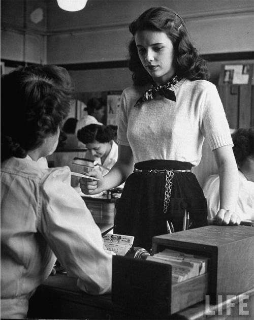 "Madeline Balcar, age 16, modeling teen-age fashions, in the library. Photograph by Nina Leen, LIFE, March 21, 1949.  ""For school, Madeline picked a trim short-sleeved sweater and black corduroy skirt with dog-leash belt and silk scarf as accessories. Total cost is $11.95."" — LIFE"