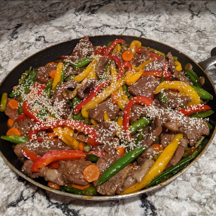 This steak stir fry with all of the vegetables is a weeknight superhero! Tender shreds of beef are tossed with five different rainbow vegetables in a paleo, gluten free, and sugar free stir fry sauce that doesn't sacrifice an ounce of flavor. Ready in just about 30 minutes, this healthy weeknight dinner is loaded with nutrients and couldn't be easier to make. #paleo #glutenfree