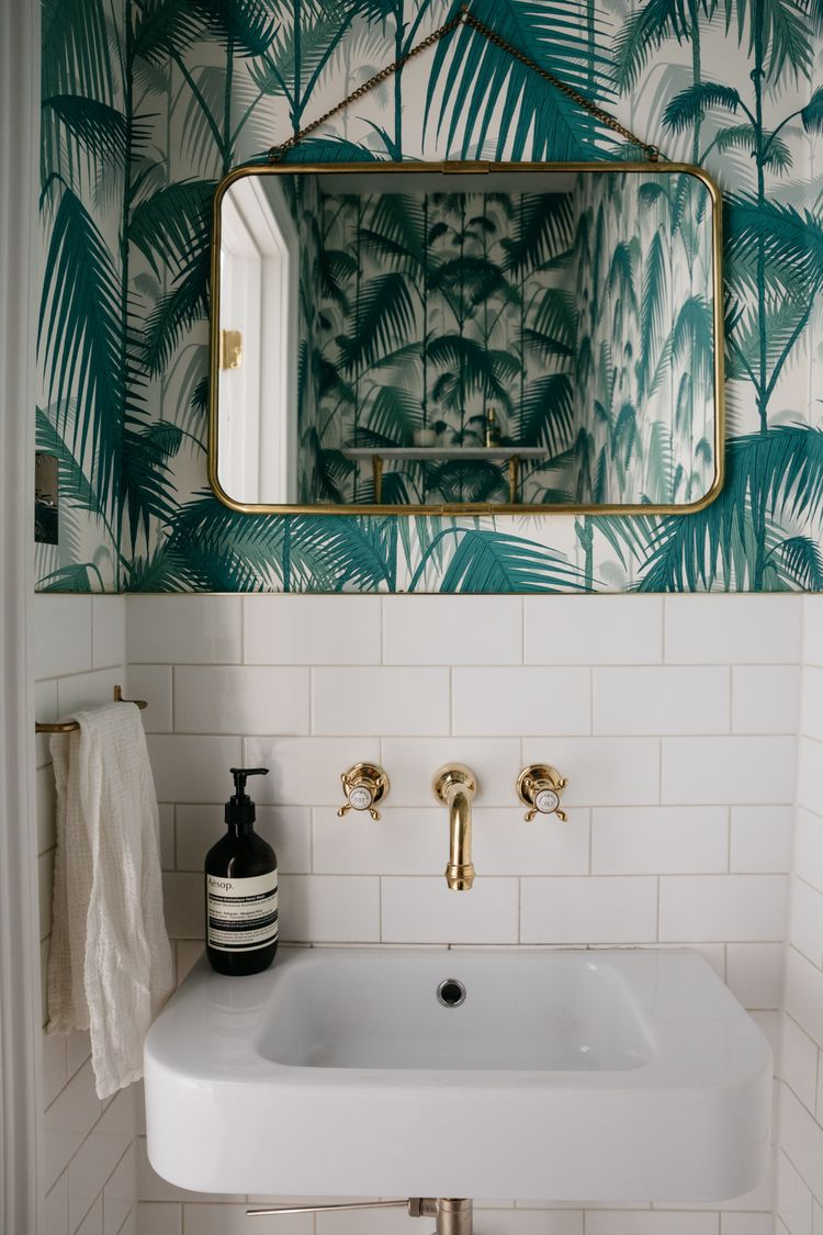 "A Brooklyn powder room papered in Cole & Son's ""Palm Jungle"" wallpaper. Photograph by Brian Ferry for Remodelista; styling by Alexa Hotz, from Before & After: A French-Inflected Townhouse Renovation in Williamsburg, Brooklyn."