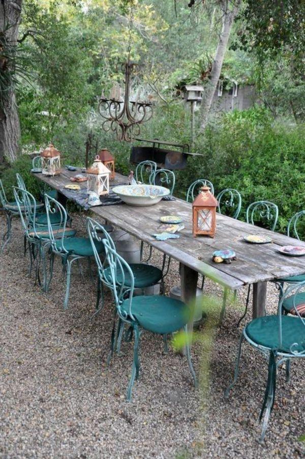 une grande table de jardin en bois, chaises en fer forgé b