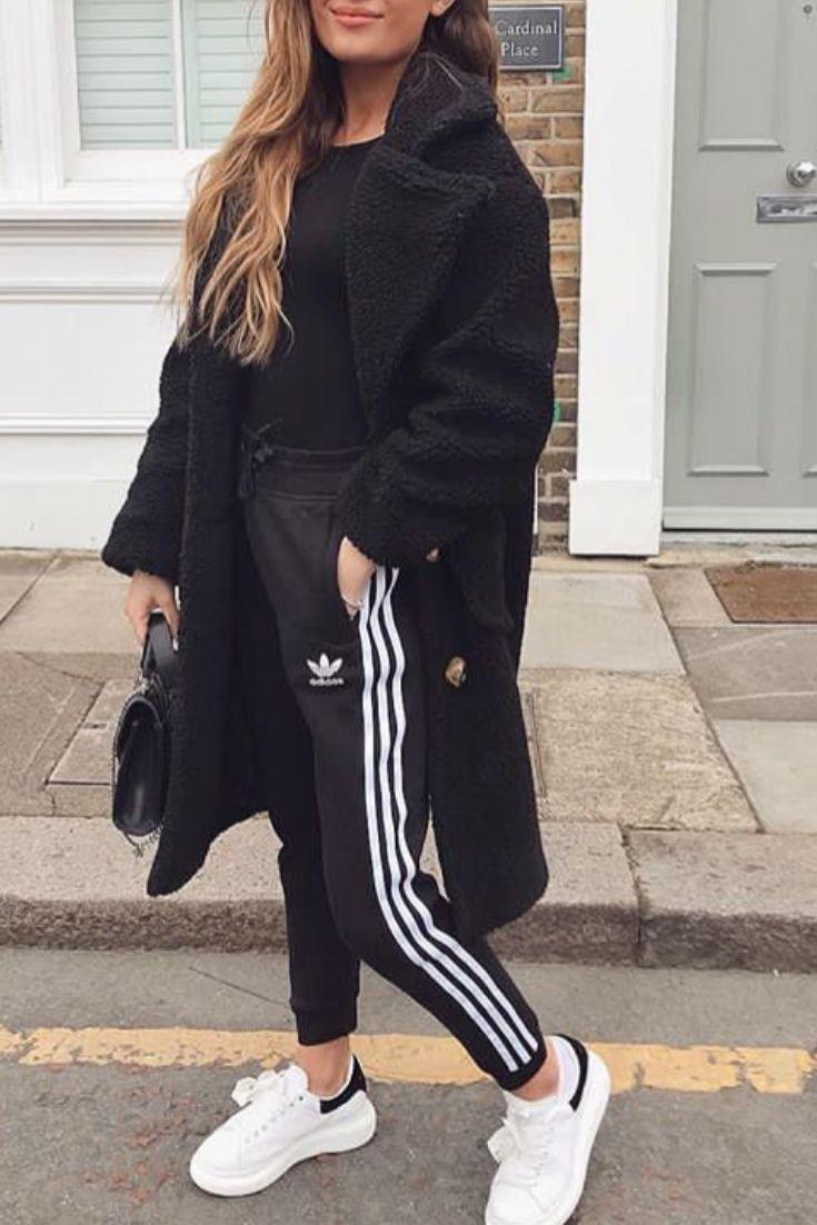 Mode femme tenue casual avec un jogging adidas, des baskets blanche et un long manteau noir en peluche