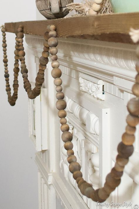 How to make a rustic wood beaded garland. Sharing how I aged the wood beads quickly and tips to thread the beads on twine. Plus, a simple tassel for the wood beaded garland ends made with twine.