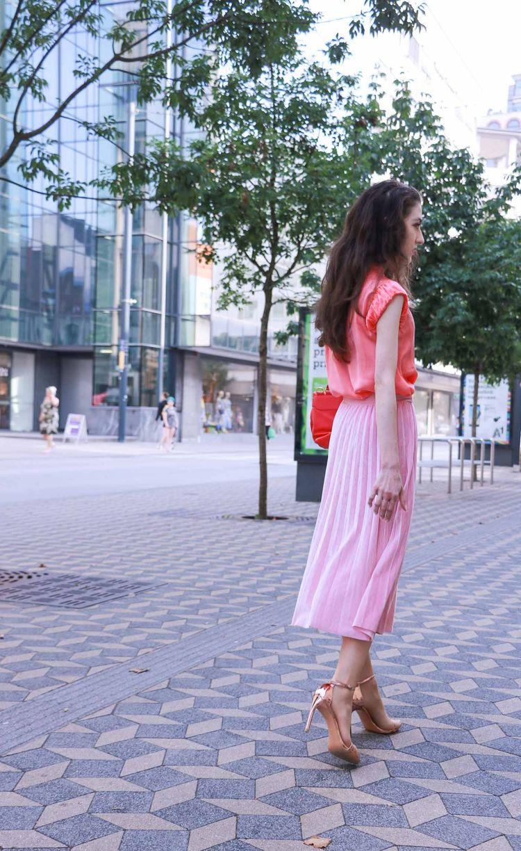 6b88ca8b98 Fashion Blogger Veronika Lipar of Brunette from Wall Street wearing round  framed sunglasses, pink pleated midi skirt, pink top, hot pink top handle  bag and ...