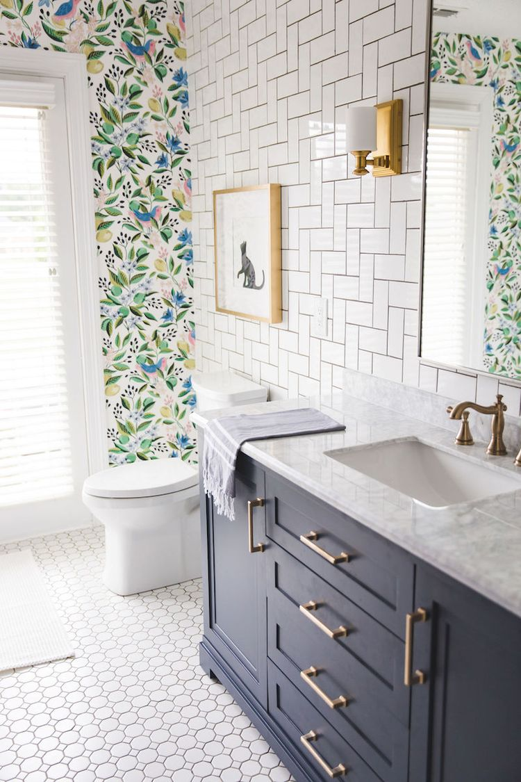 This bright bathroom was a DIY remodel!  Blogger shares tutorials from how to demo to how to tile!  #bathroomremodel #bathroomrenovation #homeremodel #homerenovation #subwaytile #floralwallpaper #goldfaucet #navyvanity