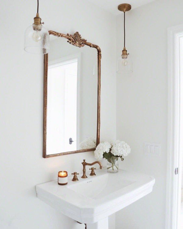 Gold antique mirror above bathroom sink