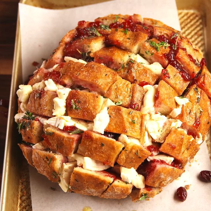 This cranberry brie pull-apart bread is the holiday appetizer no one can resist. Get the recipe at Delish.com. #delish #easy #recipe #cranberry #brie #cheese #thyme #rosemary #boule #bread #pullapart #appetizer #thanksgiving #holiday #christmas #bake #cheesy #sourdough #snack #fingerfood