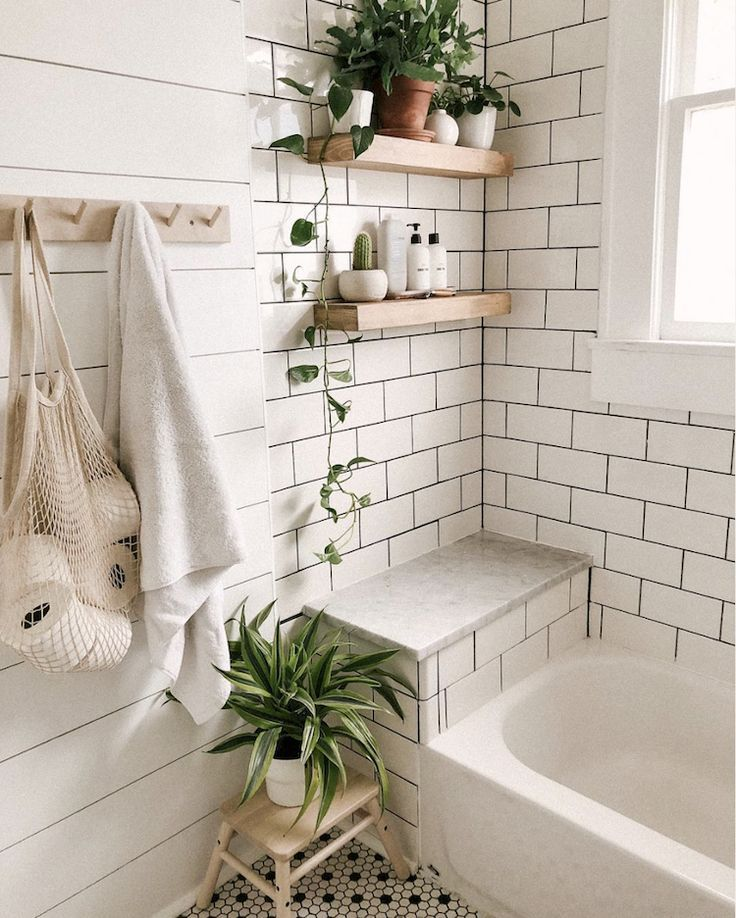 white tiles with black grouting and light wood shelves in the bathroom