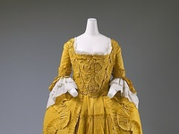 1700~1795.....During this century distiction was made between full dress worn at formal occasions and underdress for everyday clothes.  Underdress included the robe a la francaise, or the sack-back gown and the less formal robe a l'anglaise or the closed bodied gown.  Sleeves were bell or trumpeted shaped and became narrower as the century progressed.  Dark, somber colors were preferred by older women, while light and bright colors were worn by younger women.  Shoes had a high curved heel and backless mules were the most popular choice of shoe during the period.