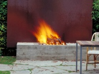 Fire as a gathering anchor in outdoor spaces.