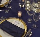 In the Navy Now: Festivities Design / If you're envisioning U.S. Navy dress blue uniforms with white piping and gold accents, we think alike. The base of this tablescape is a gorgeous navy matte satin table linen with layered gold charger plates and gold beaded glass chargers, wrapped in a navy blue sequin napkin. The mahogany chiavari chairs feature gold tufted cushions and navy matte satin sashes woven through the decorative spindles. Atop the table, varied sizes of glass cylinder vases feature gold floating candles.