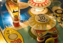 Pinball / Pinball is a type of arcade game, usually coin-operated, in which points are scored by a player manipulating one or more steel balls on a play field inside a glass-covered cabinet called a pinball machine