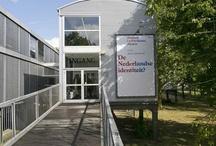 Museum De Paviljoens, Almere / Museum De Paviljoens toont hedendaagse kunst aan een hedendaags publiek in de new town Almere. Met spraakmakende tentoonstellingen, prikkelende lezingen, bijzondere festivals, excursies en vernieuwende kunstenaarsprojecten binnen en buiten de museummuren, betrekt Museum De Paviljoens Almeerders en bezoekers uit de rest van Nederland bij hedendaagse kunst. Het museum is gevestigd in de Aue Paviljoens, ontworpen door Robbrecht en Daem voor de Documenta IX (1992, curator Jan Hoet) in Kassel.