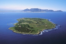 Robben Island / Most people have heard of Robben Island but many don't know just how rich in history this island really is. Robben Island is a low-lying rocky outcrop located in Table Bay, 6km west of Bloubergstrand and about 30m above sea level. The name Robben is derived from the Dutch, meaning seal. It has a Mediterranean climate, but exposed to violent winter gale force winds and tides that make its northern and western sides virtually uninhabitable.